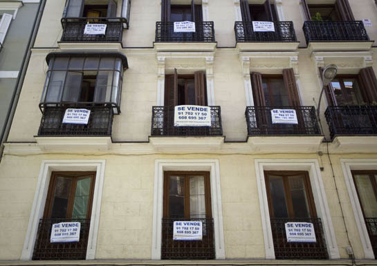 "DOCU_GRUPO Signs saying ""For Sale"" hang on the balconies of an apartment block in central Madrid"